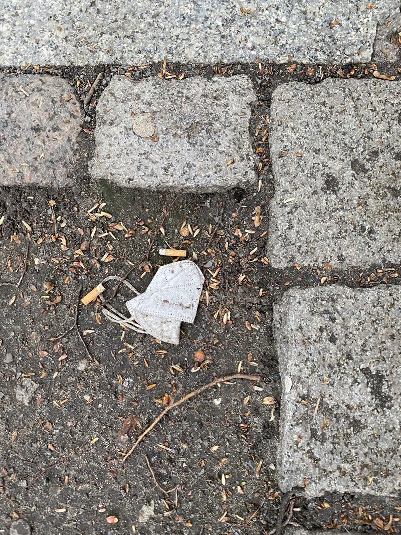 FFP-2 eingerahmt mit Zigarettenstummel